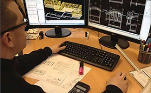 Designer at pc using model software
